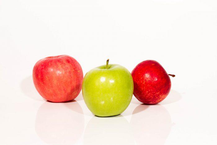 Grüner Apfel unter roten Äpfeln