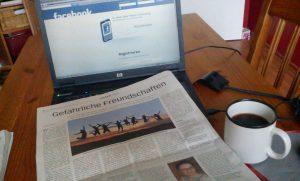 Laptop mit Zeitung und Kaffeetasse
