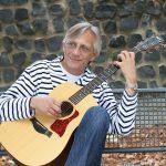 Christian Straube sitzt auf einer Bank und spielt Gitarre