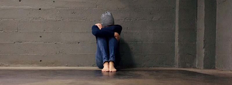 Person sitzt allein an einer Wand mit dem Kopf auf den Knien verschränkten Armen