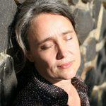 Sabria im Sonnenlicht an Steinmauer gelehnt