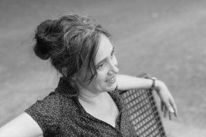 Sabria lächelnd auf einer Bank mit Blick in die Ferne