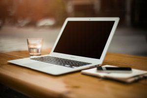 Notebook auf Schreibtisch mit Notizblock und Getränk