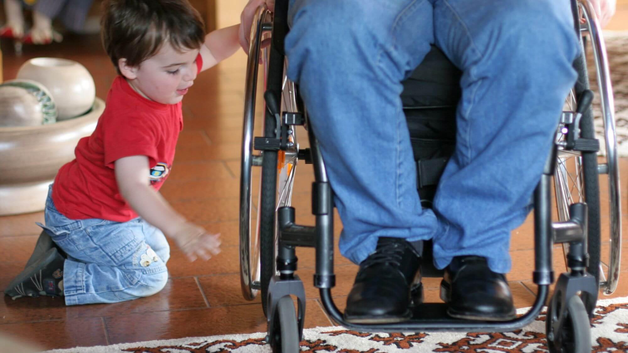 Kind spielt mit Rad eines Rollstuhlfahrers (c) Annette Schwindt