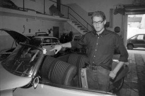 Tim zeigt auf ein Cabrio in der Schrauberwerkstatt