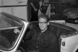Tim mit offener Fahrertür am Steuer des Cabrios