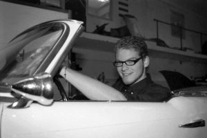 Tim am Steuer des Cabrios lächelt in die Kamera
