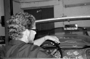 Tim von hinten am Steuer des Cabrios fotogrfiert schaut durch den Rückspiegel in die Kamera