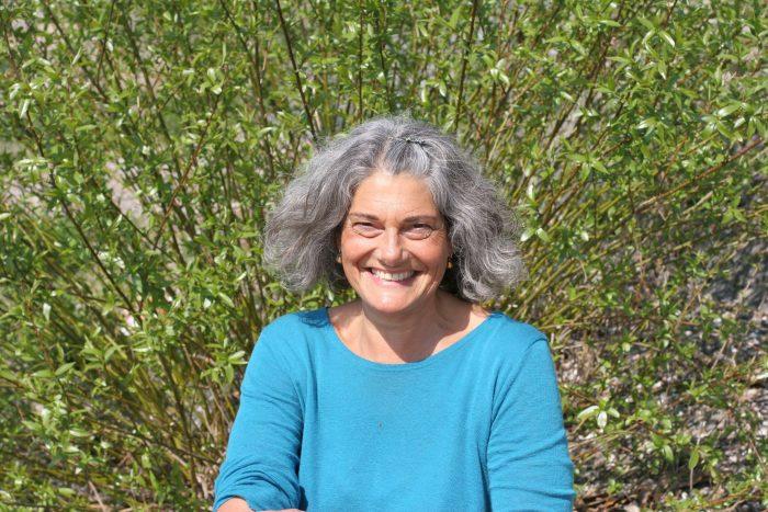 Christine pfauengleich vor einem Busch