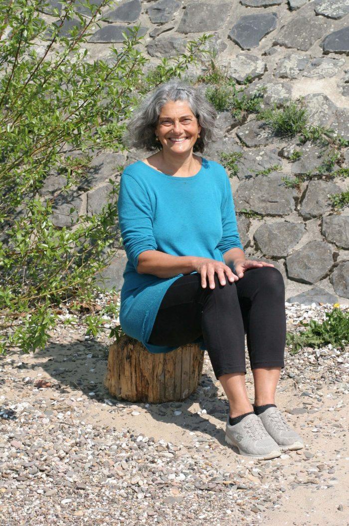 Christine sitzt am Ufer