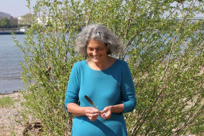 Christine spielt mit einer Feder am Rhein