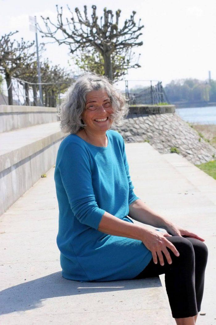 Christine sitzt auf den Treopeen am Rhein und lacht in die Kamera