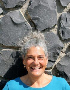 Christine mit Zopf vor Steinmauer