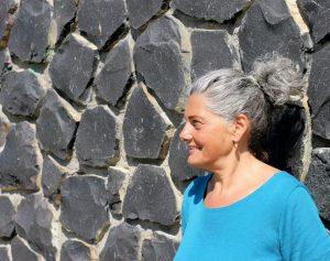 Christine mit Zopf im Profil vor Steinmauer