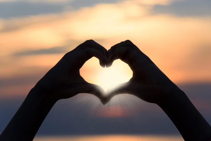 Zwei Hände formen ein Herz im Gegenlicht zum Sonnenaufgang