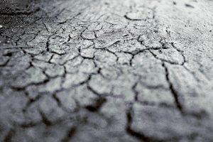 Schwarz-Weiß Foto über rissigne, vertrockneten Boden hinweg