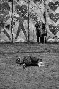 Obdachloser liegt auf Wiese vor mit Herzen bemalter Mauer, vor der ein Paar ein Selfie macht, ohne ihn zu beachten