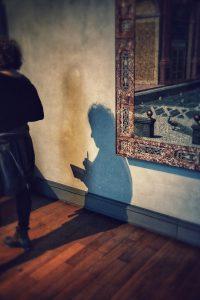 Frau geht von Bild in Museum weg, aber ihr Schatten sieht aus als ob er bleibt