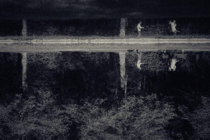 Schwarz-Weiß Foto über einen See hinweg, am anderen Ufer spiegeln sich Spaziergänger