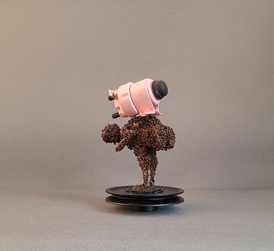 Crouching figure made of tiny metals scrapes, standing on a plastic socket balancing a pink big weight on its back