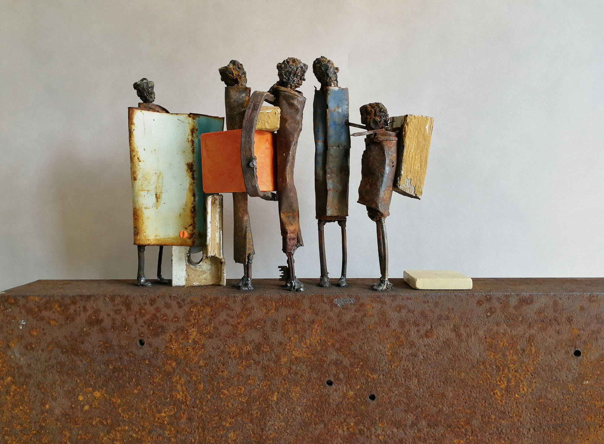 Five differntly sized and coloured metal figures standing in line