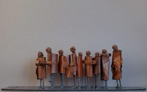 Eight metal figures standing in line behind each other looking like they'd hold each other by the waist and one bigger figure at the end oerseeing them.