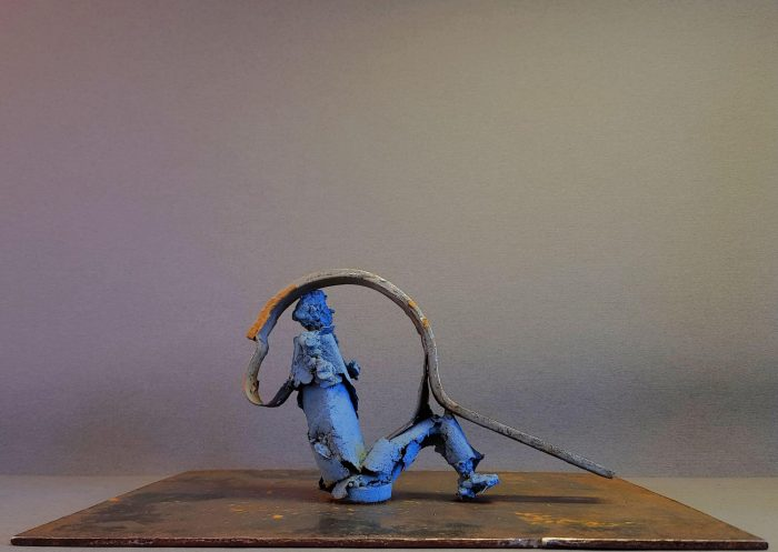 Blue metal figure sitting on a metal platform with a bent metal band going over its knees and head to its back
