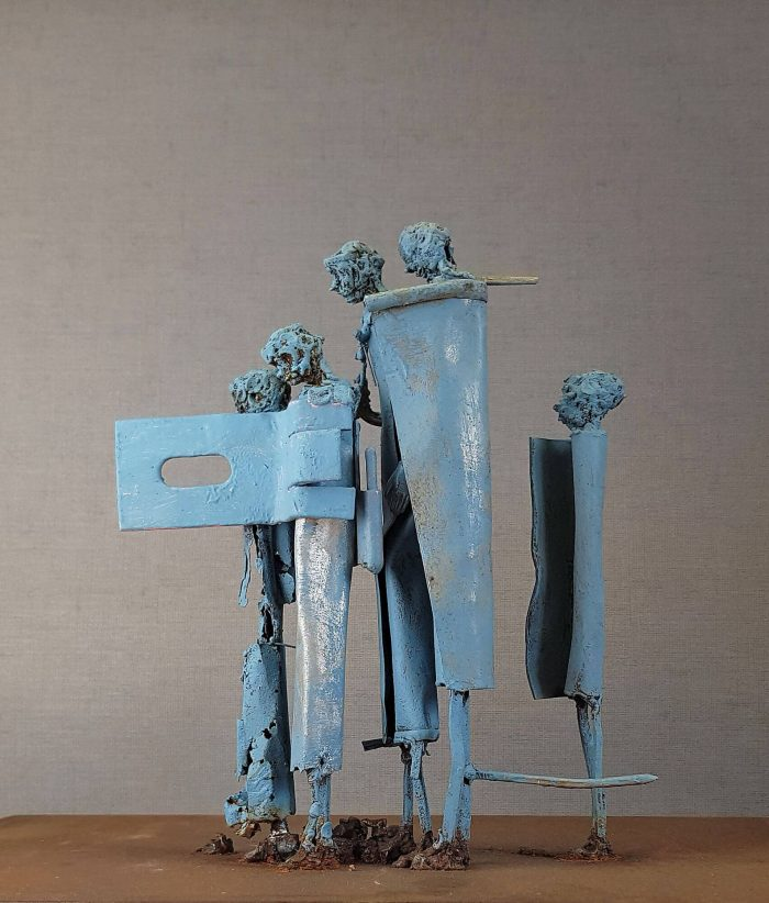 Five light blue coated metal figures one behind each other looking to the left.
