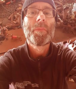 Selfie of Johan with beard and glasses with the metal junk in the background that he makes his sculptures of