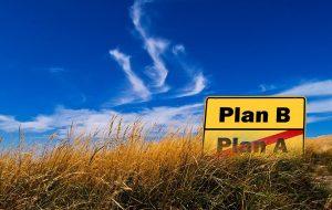 In einer Wiese steht ein Schild, auf dem Plan A durchgestrichen ist, und darüber steht Plan B
