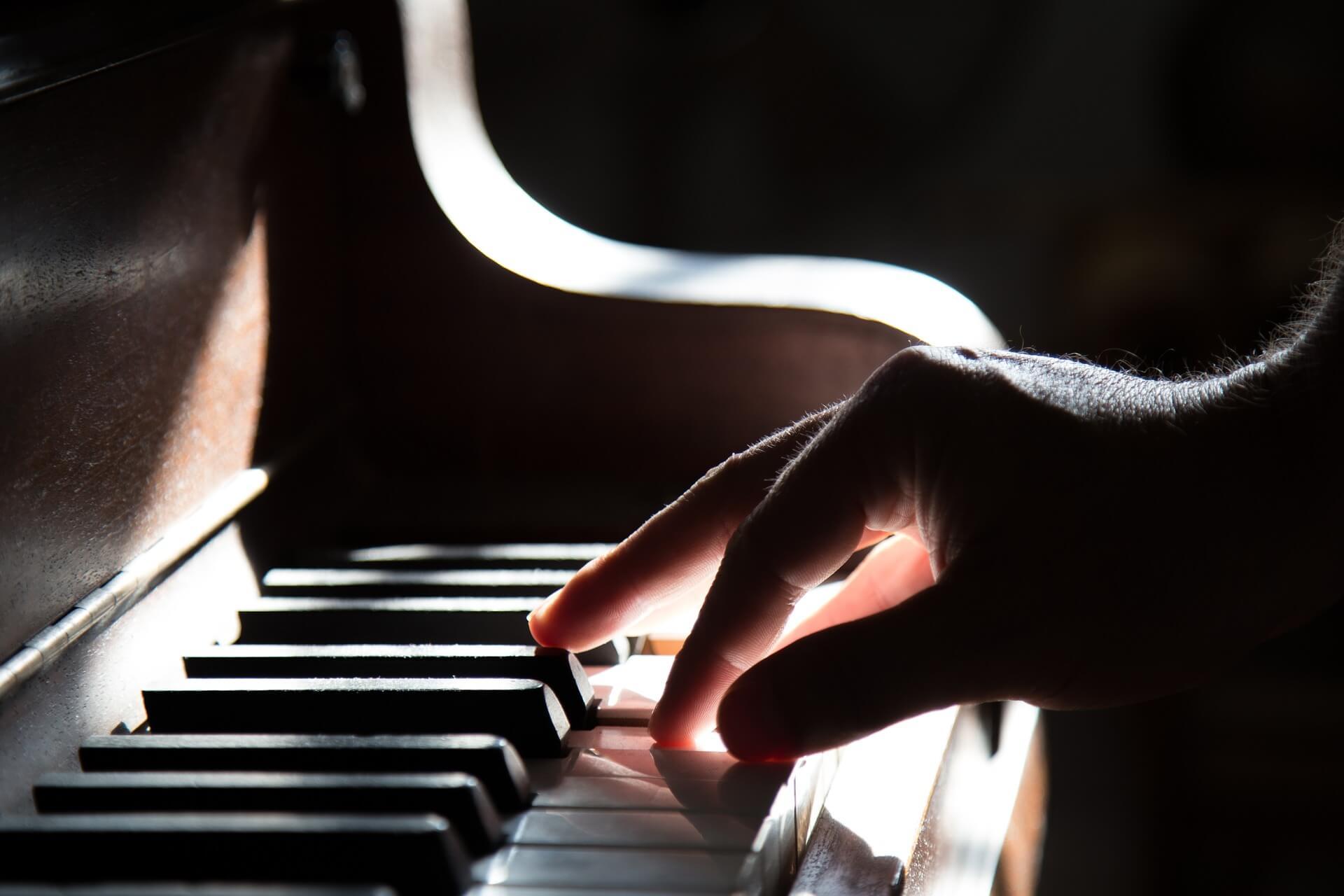 Klavierspielende Hand im Gegenlicht