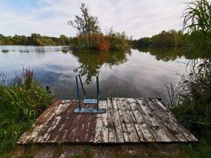 Verwiterter Badesteg mit Blick auf den See