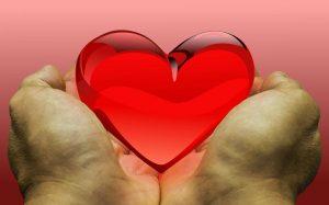 Zwei Hände halten ein gläsernes Herz