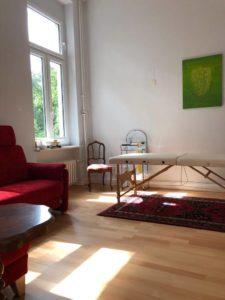 Behandlungsraum mit dem Gemälde an der Wand über der Therapieliege