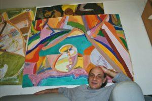 Renato zuahuse vor mehreren seiner Bilder