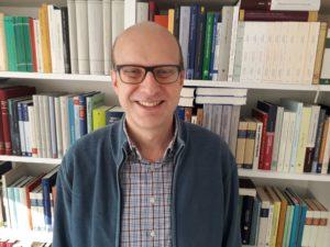 Dr. Michael Schramm vor seinem Bücherregal