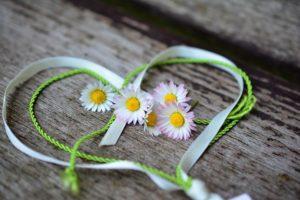 Aus weißen und grünen Bändchen geformtes Herz mit Gänseblümchen auf Holz