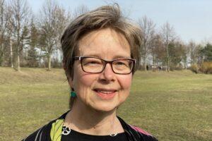 Andrea Kamphuis lächelt auf einer Wiese mit Bäumen im Hintergrund in die Kamera