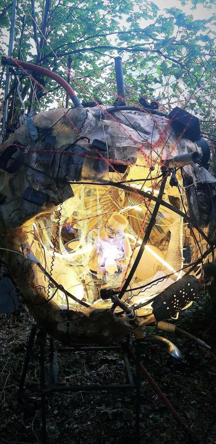 Installlation von Martin Eckrich im Kunstgarten: Raumschiffartiges Kugelgebilde hängt mit Drähten und SChnüren zwischen Bäumen, innen beleuchtet sitzt ein lesendes Männchen mit Brille
