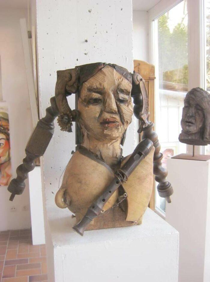 Holzskulptur eines weiblichen Torsos mit Zöpfen aus Tischbeinen, einer Flöte, einer zerbrochenen Amphore als Brust