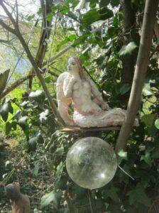 Im Baum sitzende Frauenskulptur über einer gläsernen Blase
