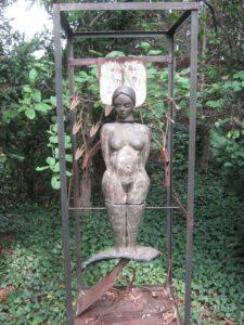 Frauenskulptur in Metallgerüst mit Garten im Hintergrund
