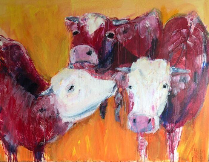 Zwei braunbunte Kühe vor orangefarbenem Hintergrund