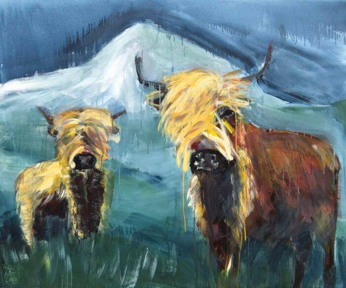Zwei haarige Hochlandrinder vvor graublauem Hintergrund mit Berg