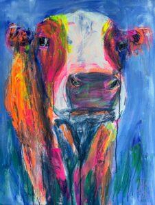 Bunte Kuh vor blauem Hintegrund schat den Betrachter an